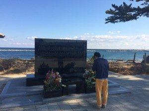原釜の慰霊碑。黄色いズボンの当社社員。